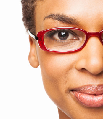 Close-up portrait of a smiling African American woman in spectacles. Horizontal shot. Isolated on white.